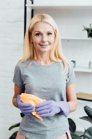 lächelnde reife Frau in Gummihandschuhen mit Tuch
