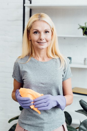 smiling mature woman in rubber gloves holding cloth