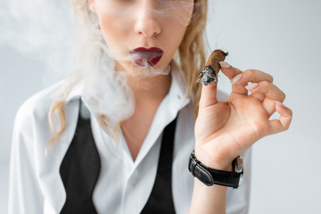 cropped view of fashionable blonde girl smoking cigar on grey 版權商用圖片