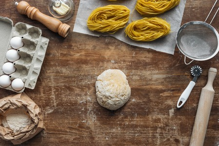 top view of uncooked formed dough and pasta ingredients on wooden table