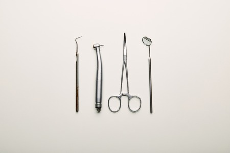 flat lay with stainless dental instruments arranged on white tabletop, dentistry concept