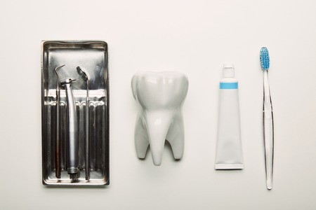 flat lay with stainless dental instruments in container, tooth model, toothbrush and paste arranged on white tabletop