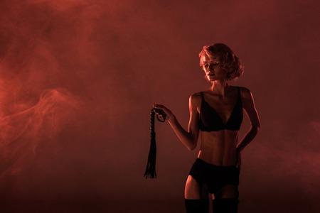 Schöne verführerische Frau in wundervollen Dessous mit Peitsche auf rotem Rauchhintergrund Standard-Bild