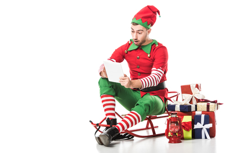 surprised man in christmas elf costume sitting on sleigh near pile of presents and looking at wishlist isolated on white