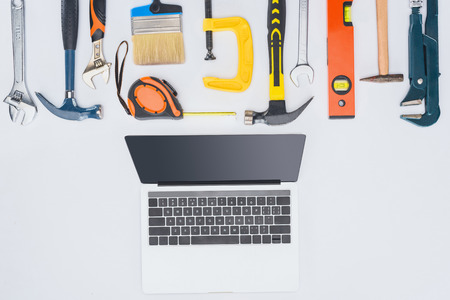 top view of laptop with different tools lying on white Stock Photo