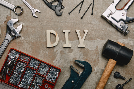 Top view of do it yourself sign and various carpentry tools arranged on old  surface background
