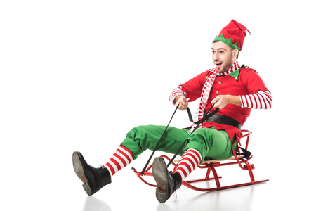excited man in christmas elf costume riding sleigh isolated on white background