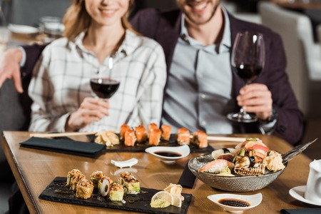 Partial view of smiling couple eating sushi and drinking wine in restaurant 免版税图像