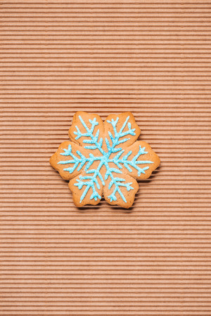top view of of snowflake gingerbread cookie on the textured background