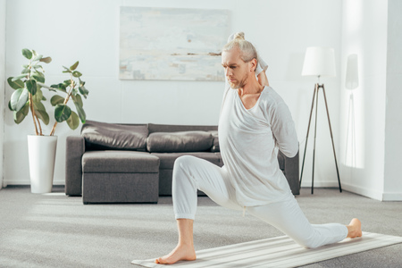 man practicing Crescent Lunge on the Knee yoga pose at home