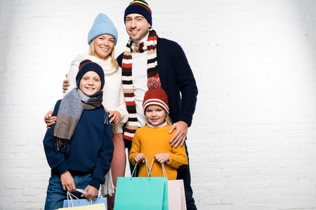 happy family in winter clothes looking at camera and holding shopping bags
