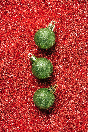 top view of green shiny decorative christmas balls on red sequin background Stock Photo