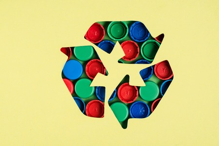 Top view of recycle sign with bottle caps pattern on yellow background