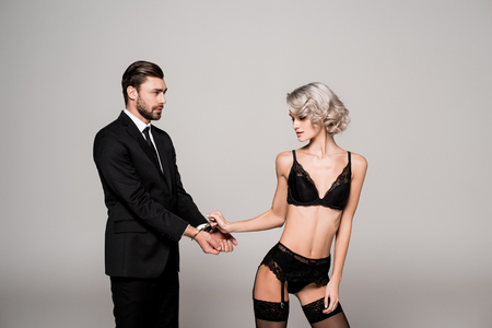 Seductive woman holding hands of handsome man in handcuffs in lingerie isolated on grey Stock Photo