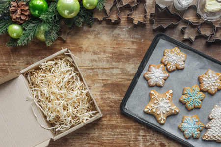 flat lay with christmas cookies on baking pan, christmas wreath, cardboard box and cookie cuttrers on wooden surface