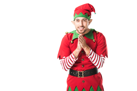 smiling man in christmas elf costume looking at camera and rubbing hands in anticipation isolated on white