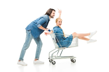 Happy couple having fun with shopping cart isolated on white