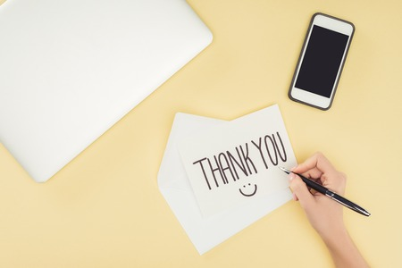 cropped person holding pen above white postcard with thank you lettering, smartphone and laptop isolated on yellow background