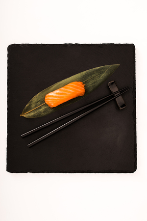Top view of nigiri sushi with shrimp served with chopsticks on black slate