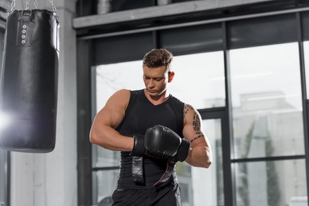 low angle view of handsome muscular boxer wearing boxing gloves in gym