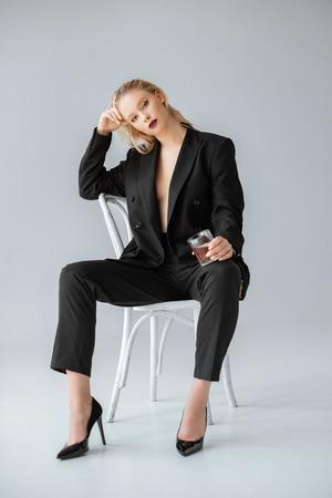 femme à la mode en tenue de soirée avec un verre de whisky assis sur une chaise sur fond gris Banque d'images