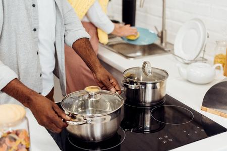Cerca del hombre afroamericano sosteniendo la olla mientras la mujer lava los platos en la cocina