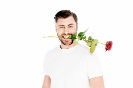 Handsome man holding red rose in mouth isolated on white