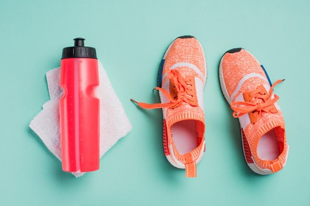Top view of sneakers, sport bottle and towel on turquoise background 版權商用圖片