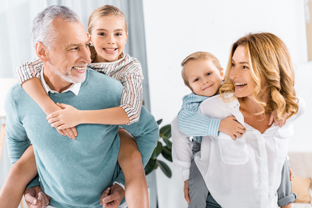 laughing grandparents doing piggyback ride to adorable grandchildren at home