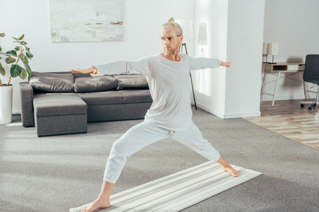full length view of man standing in warrior yoga pose on mat at home Stock Photo
