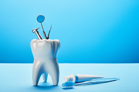 close up view of white tooth model, toothbrush, toothpaste and stainless dental instruments on blue backdrop Banque d'images - 112334893