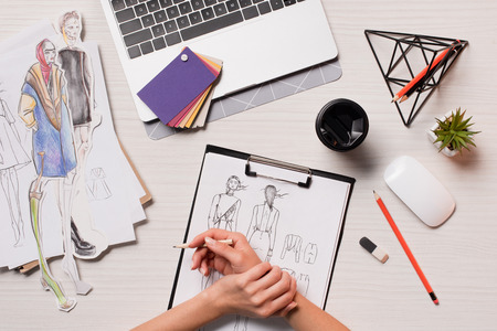 office desk with laptop, art supplies and cropped view of designer working on sketches, flat lay