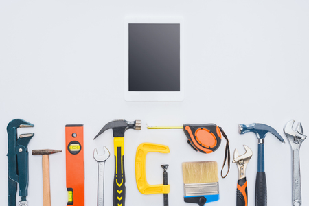 top view of tablet with various tools lying on white
