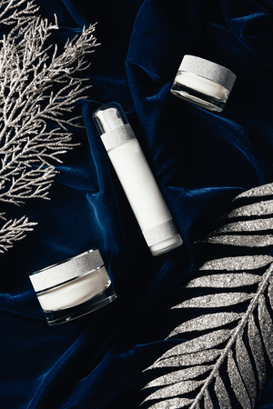 view from above of lotion and beauty cream between christmas silver branches on velvet surface Banque d'images