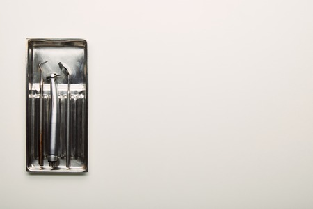 top view of stainless dental instruments in container on white tabletop Banque d'images - 112335254