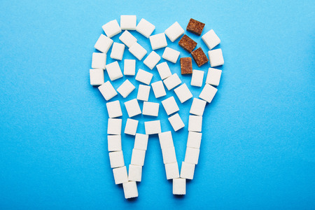 top view of white and brown sugar cubes arranged in tooth sign on blue background, dental caries concept