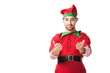 man in christmas elf costume with outstretched hands gesture looking at camera isolated on white