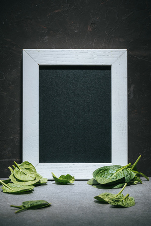 Blank board in white frame with fresh picked spinach leaves Stockfoto