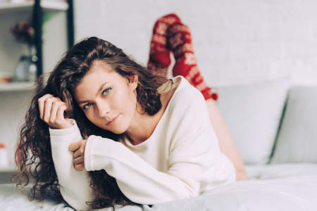 pretty young girl in white sweater and red socks looking at camera in bedroom at home Reklamní fotografie