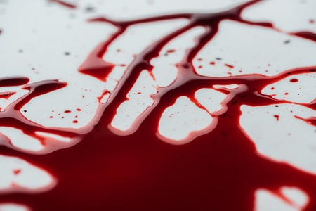 close-up shot of messy blood droplets on white surface