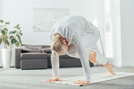barefoot adult man doing lunge yoga exercise on mat at home