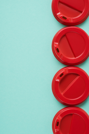 Top view of  four red disposable lids for drink arranged on blue background