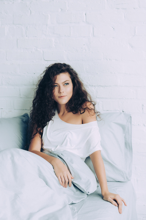 happy woman sitting in bed during morning time at home