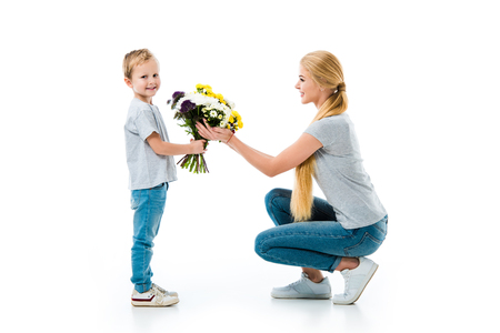 Beautiful mother with cute son holding flowers isolated on white