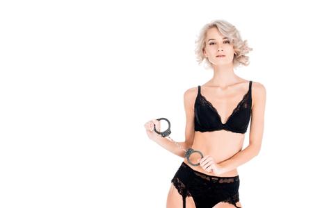 Atrakcyjna uwodzicielska blondynka w bieliźnie trzymająca kajdanki na białym tle Zdjęcie Seryjne