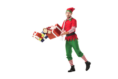 surprised man in christmas elf costume accidentally dropping pile of presents isolated on white
