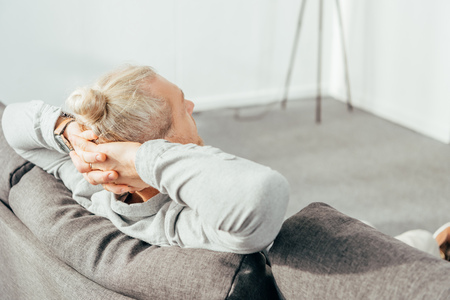 back view of man resting with hands behind head on couch