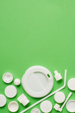 Top view of disposable plastic bottle caps, drinking straw and lid for drink on green background