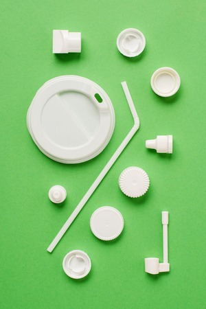 Top view of plastic bottle caps, drinking straw and lid for drink on green background Stock Photo