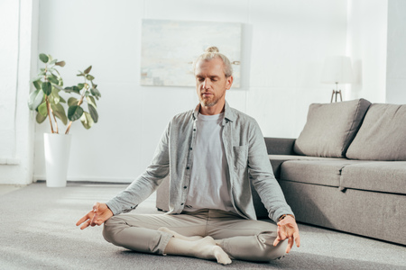 sporty adult man meditating in lotus position at home